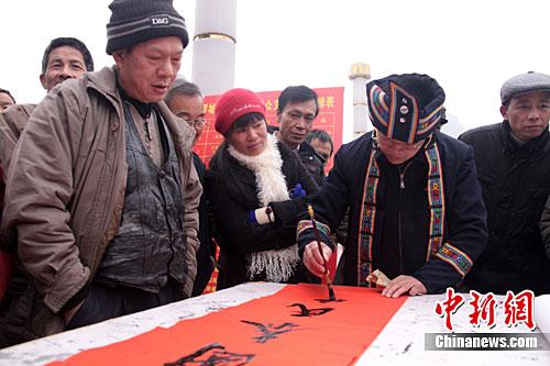 春节将至 仫佬族书法家免费给群众送春联